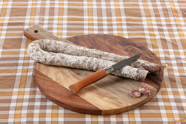 Curved dry sausage on cutting board