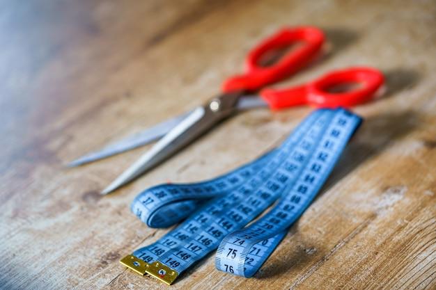 Изогнутая измерительная синяя лента на деревянном столе. ножницы с красной ручкой на деревянном столе. концепция портного.
