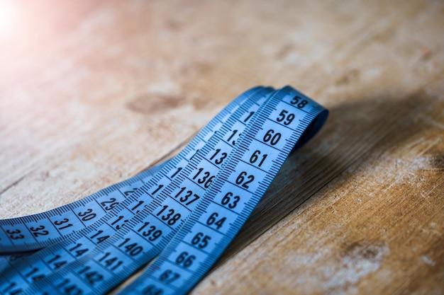Изогнутая измерительная синяя лента на деревянном столе. концепция портного. концепция диеты и диеты.