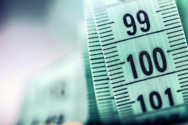 곡선 측정 테이프. 재단사의 측정 테이프. 녹색 측정 테이프의 근접 촬영 보기입니다.