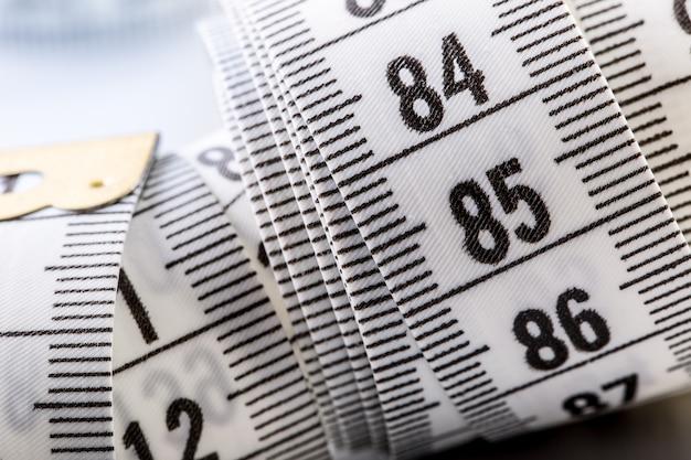 곡선 측정 테이프. 재단사의 측정 테이프. 흰색 측정 테이프의 근접 촬영 보기