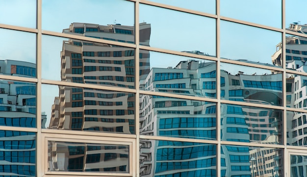 Curved modern buildings reflected in the mirrored windows