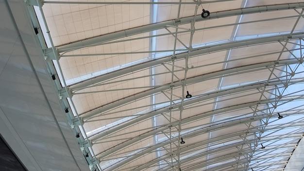 Кривая крыша с окнами большого торгового центра в закрытом помещении. современная конструкция потолка из металла и стекла.