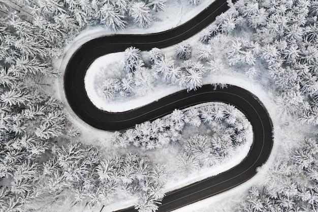 Изогнутая s-образная дорога в зимнем лесу с высоты птичьего полета.