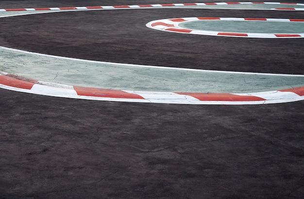 レーストラックの詳細のアスファルトの赤と白の縁石のカーブ、モータースポーツレーシングサーキットカーレース用のレーストラック曲線道路