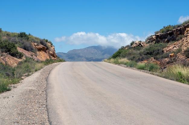산과 극적인 하늘의 전망과 함께 위쪽으로 굽은 사막 도로
