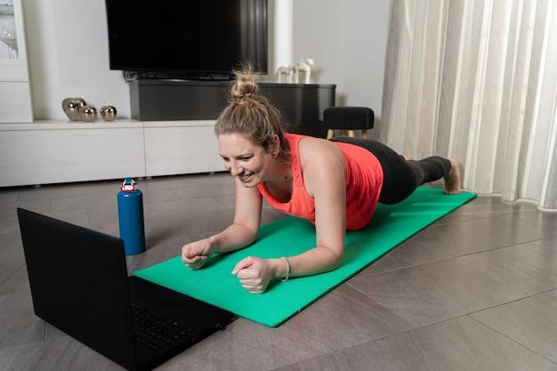 静かで笑顔の方法で自宅でスポーツを練習している曲線美の金髪白人女性。