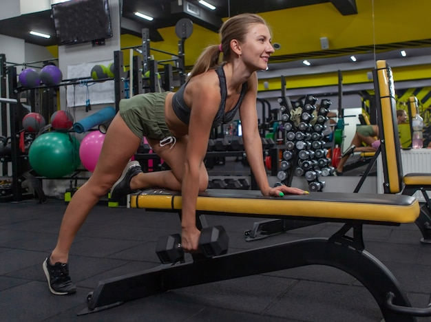 Curvy fit young woman lifting dumbbell with one arm in a gym