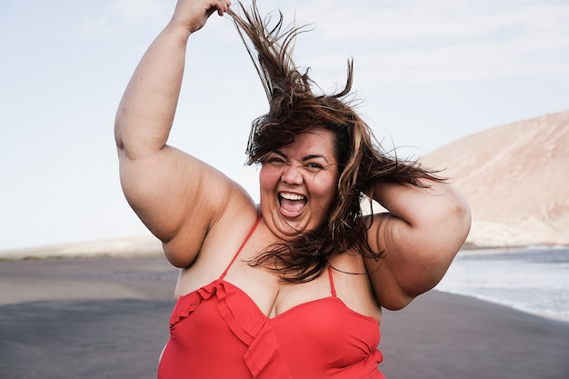 해변에서 웃는 매력적인 과체중 여자-얼굴에 초점