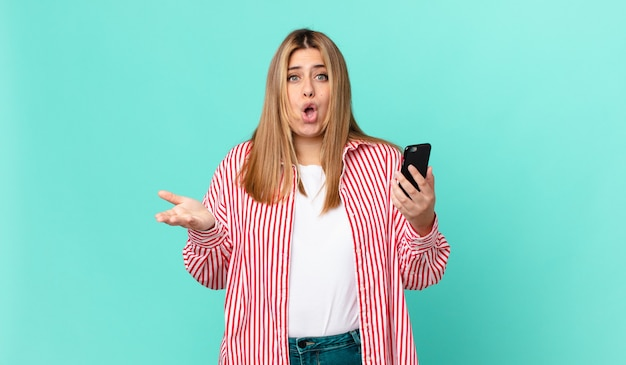 非常にショックを受けて驚いて、スマートフォンを持っている曲線美のきれいなブロンドの女性