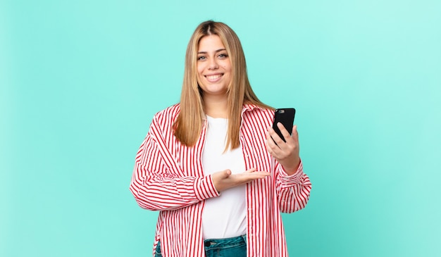 매력적인 금발 여성은 즐겁게 웃고 행복하고 개념을 보여주고 스마트 폰을 들고 있습니다.