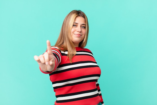 誇らしげにそして自信を持ってナンバーワンを作って笑っている曲線美のきれいなブロンドの女性