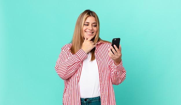 あごに手を当てて、スマートフォンを持って幸せで自信に満ちた表情で笑っている曲線美のきれいなブロンドの女性