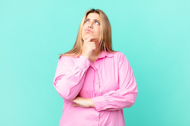 Curvy pretty blonde woman thinking, feeling doubtful and confused