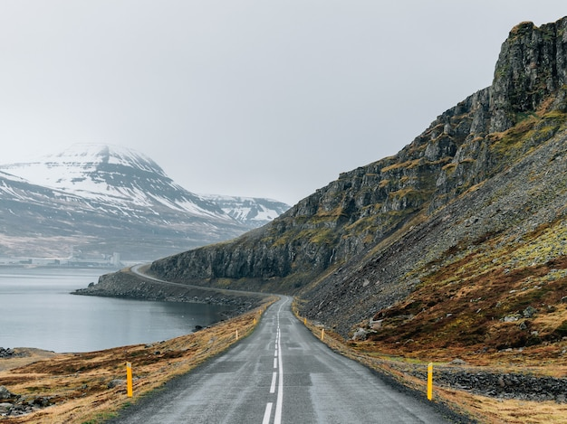 Curvy road surrounded by the sea and rocks covered in greenery and snow under a cloudy sky