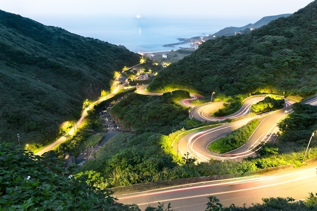 A curvy road through the grassy hills at twilight