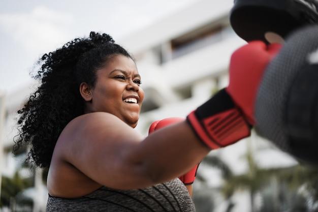 Фигуристая женщина и личный тренер делают тренировку по боксу на открытом воздухе - фокус на лице