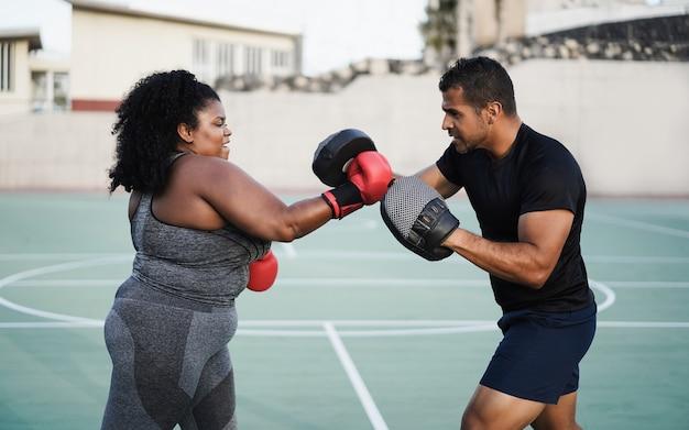 Фигуристая женщина и личный тренер проводят тренировку по боксу на открытом воздухе - основное внимание уделяется лицу тренера