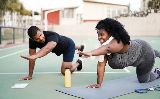 Фигуристая женщина и личный тренер делают тренировку по пилатесу на открытом воздухе - основное внимание уделяется лицу девушки