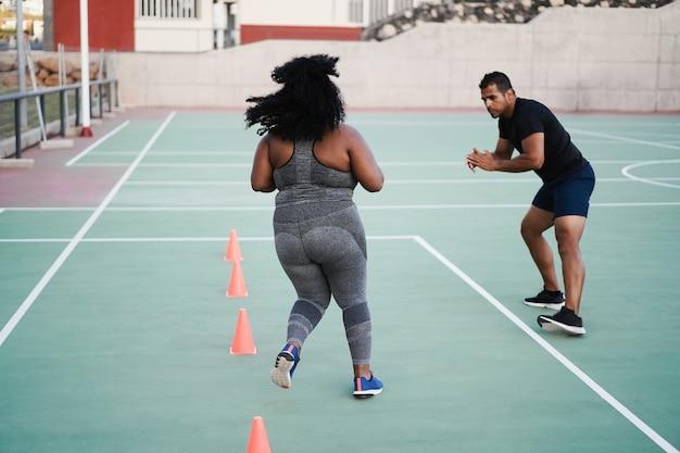 スピードと敏捷性のコーンドリルトレーニングセッションを屋外で行う曲線美の女性とパーソナルトレーナー