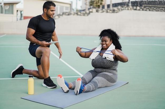 曲線美の女性とパーソナル トレーナーが屋外でトレーニング セッションを行う