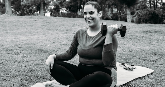 都市公園で屋外のトレーニングルーチンを行う曲線美の女性-顔に焦点を当てる