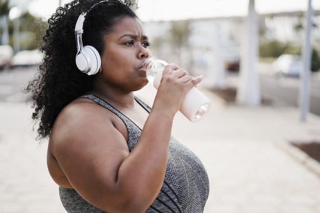 Фигуристая женщина пьет во время бега на улице в городском парке