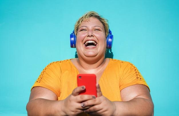 매력적인 여자 웃음과 스마트 폰 야외 사용-휴대 전화에 재미 듣는 음악 재생 목록을 가진 젊은 여성