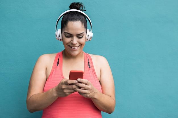 Фигуристая женщина слушает музыку из плейлиста с помощью мобильного телефона после пробежки на открытом воздухе