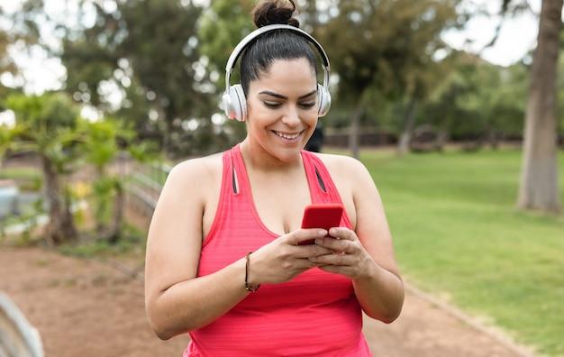 都市公園で屋外のジョギングルーチンをしながら携帯電話を使用してプレイリストの音楽を聞いている曲線美の女性-顔に焦点を当てる