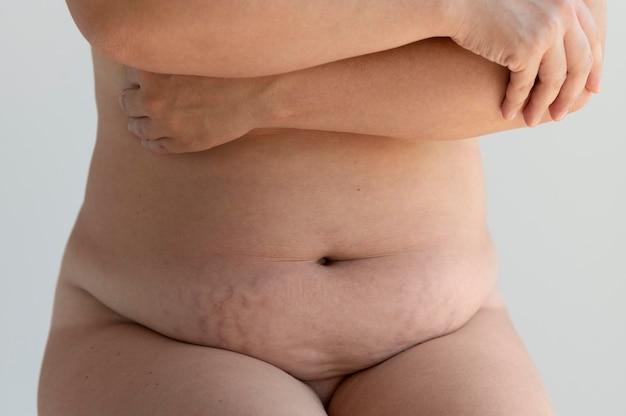 裸で自信を持ってポーズをとって肌を見せている曲線美の女性