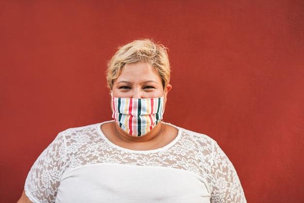 얼굴 보호 마스크를 착용하는 동안 카메라에 웃 고 매력적인 여자-코로나 바이러스 라이프 스타일 개념