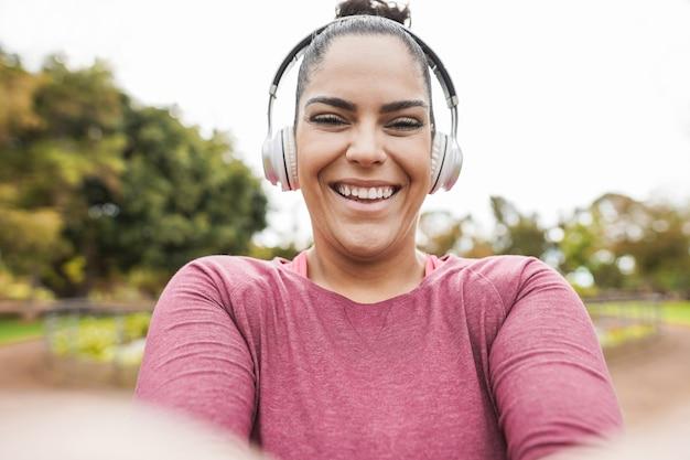 都市公園で屋外のジョギングルーチンをしながらスマートフォンで自分撮りをしている曲線美の女性-プラスサイズとトレーニングエクササイズの概念