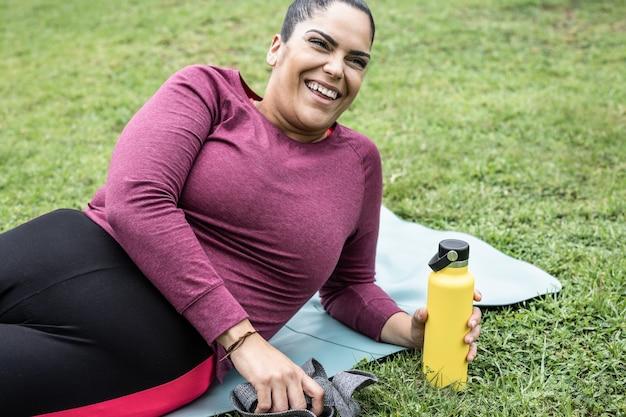 都市公園で屋外のトレーニングルーチンをしながらスマートフォンで自分撮りをしている曲線美の女性-プラスサイズと健康的なスポーツライフスタイルの概念-水筒を持っている手に焦点を当てる