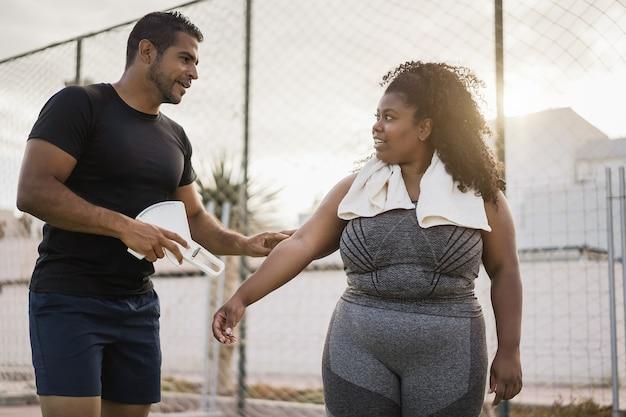屋外で体脂肪を測定するパーソナルトレーナーと曲線美の女性-アフリカの女の子の顔に焦点を当てる