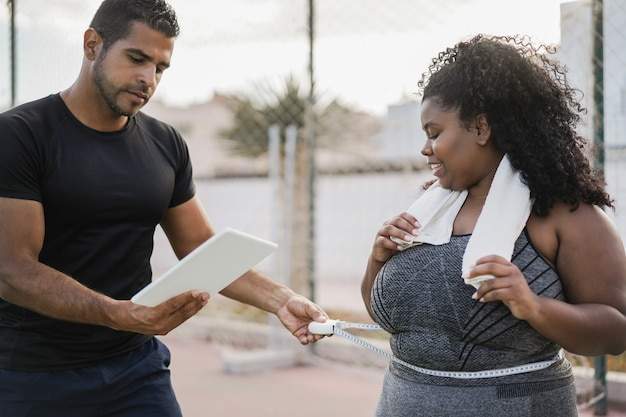 Curvy woman with her personal trainer measuring body waist outdoor - focus on african girl face