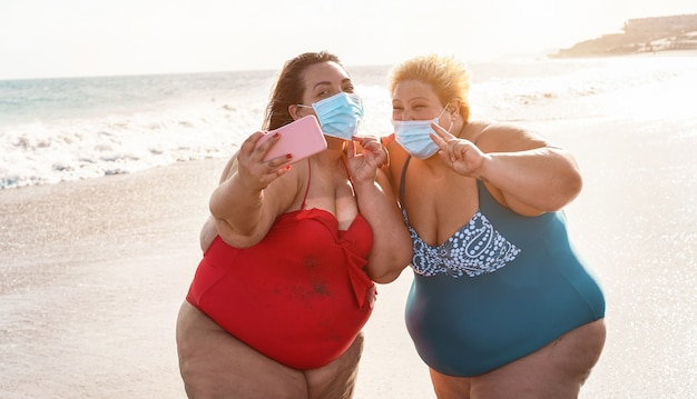 Curvy women friends taking selfie on the beach while wearing face mask for coronavirus spread prevention - summer and healthcare concept