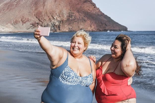 Фигуристые подруги делают селфи на пляже