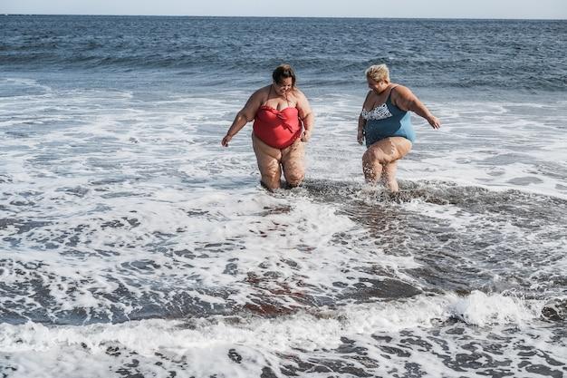 여름 시간에 재미 해변에서 노는 매력적인 여성