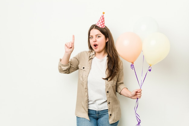 Молодые плюс женщина размера curvy празднуя день рождения имея идею, концепцию воодушевленности.