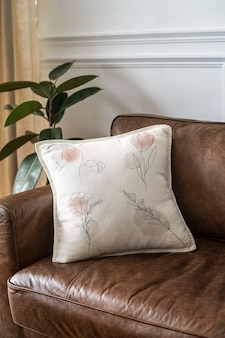Cushion with minimal floral line art on a leather couch