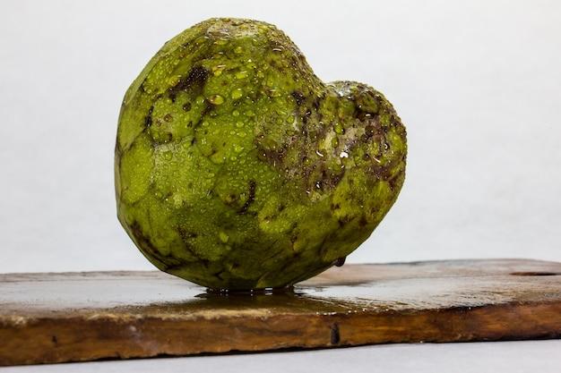 커스터드 애플 전형적인 페루 과일 과일 녹색 껍질의 근접 촬영과 나무 판자 및 흰색 배경에 물 방울