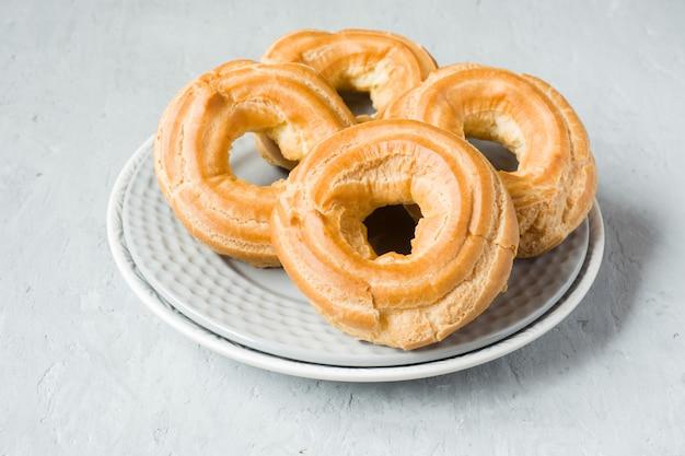 Custard cake rings on a plate on grey