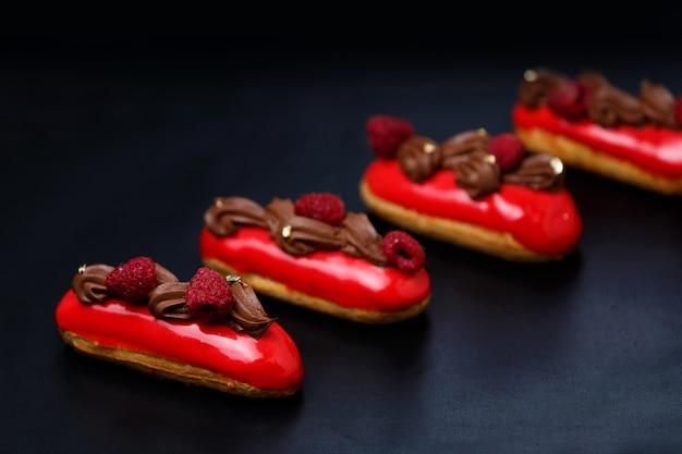 色付きのチョコレート釉薬とラズベリーとカスタードケーキエクレアは黒い背景にクローズアップ