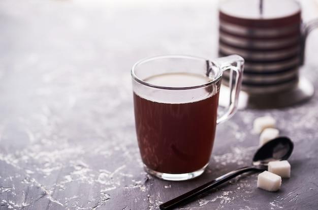 Custard coffee in a glass cup, spoon, sugar cubes, custard on a concrete background.
