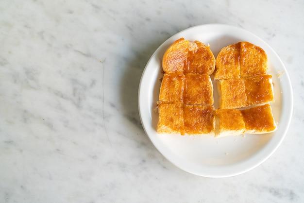Заварной крем с поджаренным хлебом на белой тарелке
