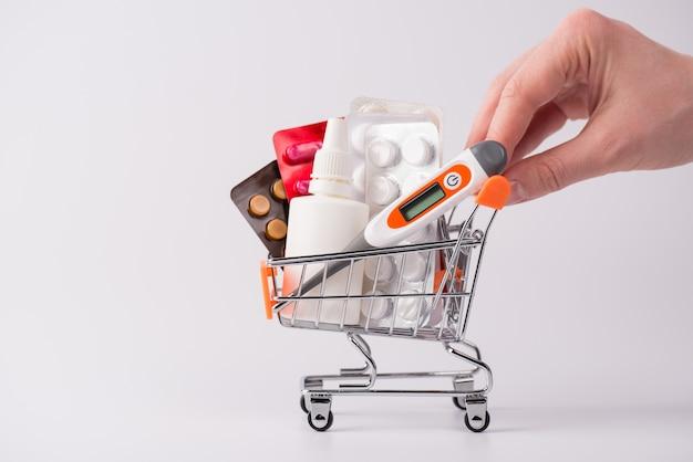 ピルのコンセプトを大量に購入する顧客。空白の空のコピースペースで灰色の背景を分離したさまざまな薬でいっぱいのショッピングカートを押す手のクローズアップ写真をトリミング