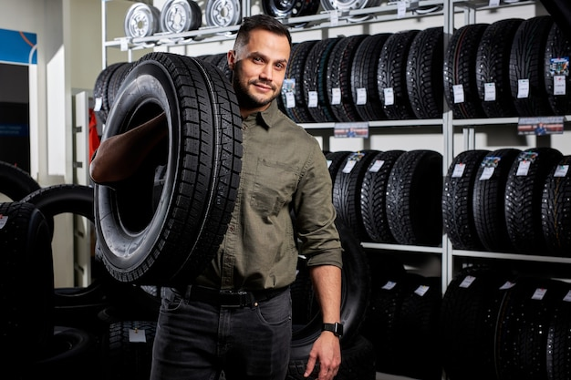 Customer in car auto repair or maintenance shop service station with automobile wheel tire, wearing casual clothes.auto, car, transport concept