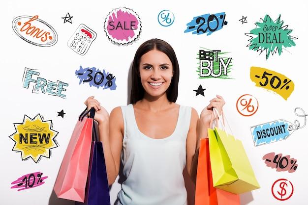 顧客の選択。カラフルな買い物袋を運び、カメラを見てドレスを着た陽気な若い女性
