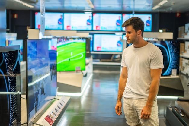 Покупатель выбирает современный телевизор в магазине